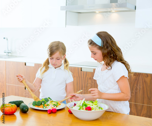 Beautiful chef sisters at home kitchen preparing salad
