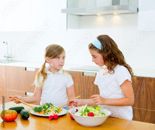 Beautiful chef sisters at home kitchen preparing salad