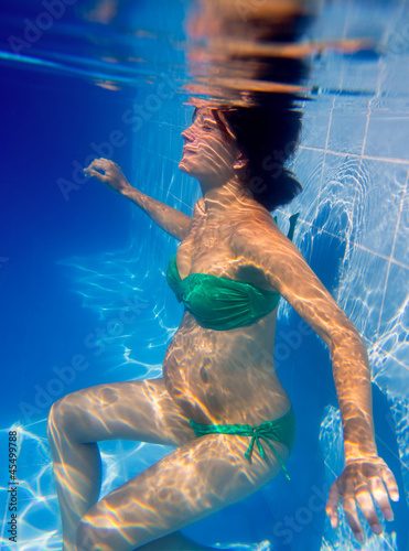 Beautiful pregnant woman underwater blue pool