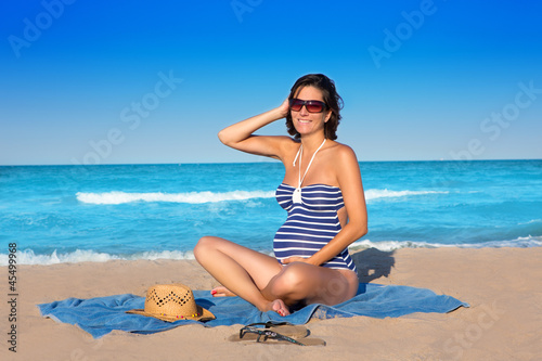 Beautiful pregnant woman sitting on blue beach sand