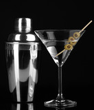 Martini glass with olives and shaker isolated on black-