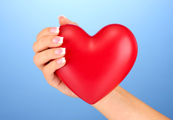 Red heart in woman's hand, on blue background close-up