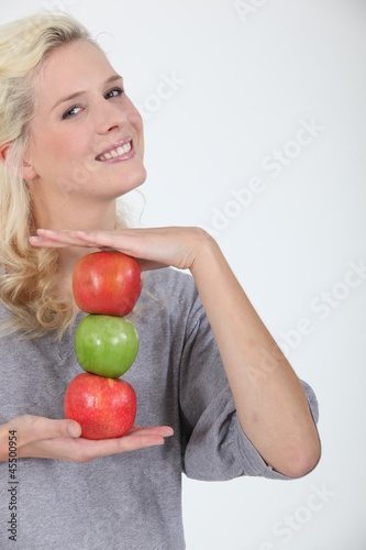 woman holding three apples
