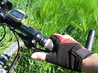 Hand in a glove on the handlebar of a mountain bike