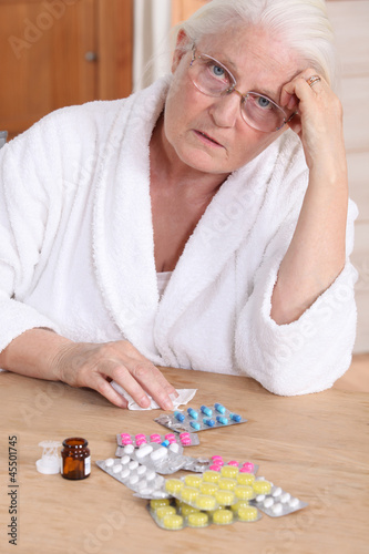 Senior woman in bathrobe about to take drugs