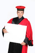 Man in red and black robe and cap pointing at board for text