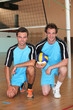 Team mates kneeling with volley ball on indoor court