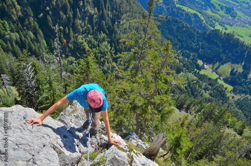 Junge klettert an Felswand