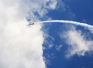 Aircraft with smoke trail on sky background