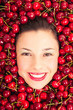 Young woman smiling face portrait surrounded by cherries.