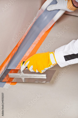 worker apply hydro insulation tape around the wall and floor