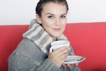 Frau wärmt sich am heißen Getränk auf