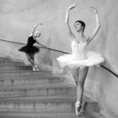Young beautiful dancers along the stairs. Black and white image.