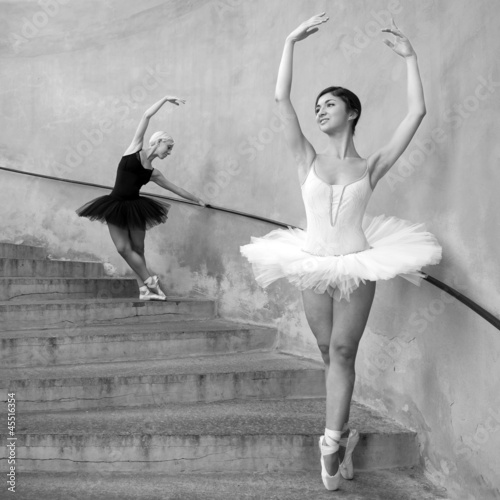 Wall mural Young beautiful dancers along the stairs. Black and white image.