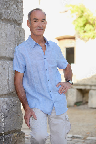 Senior man leaning on stone wall