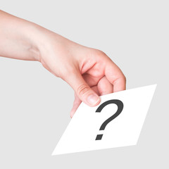 """Female hand with the white card with """"?"""" symbol"""