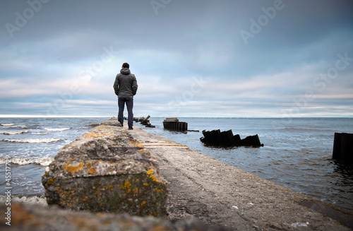 A man on the old broken pier starring at the Sea