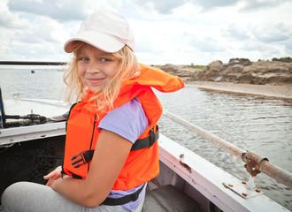 Little girl on a small boat wears bright orange life-jacket