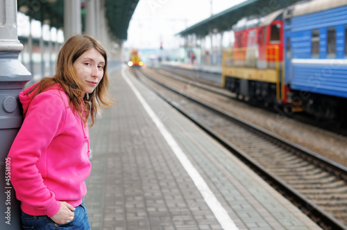 Girl waiting train on railway station platform