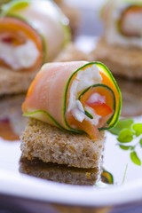 Courgette and salmon rolls with goats cheese on bread
