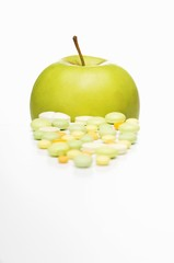 Vitamin tablets and a Golden Delicious apple