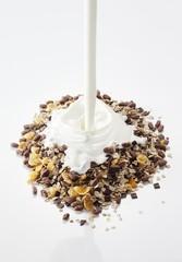 Yogurt being poured onto muesli