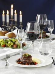 Beef medallions with vegetables, salad and red wine on a laid table