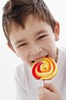 A little boy biting into a lolly