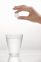 A hand holding an effervescent tablet over a glass