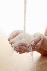 Raw sugar flowing into hands