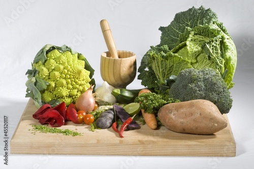 Vegetable still life with mortar and pestle with rose petals on a cutting board