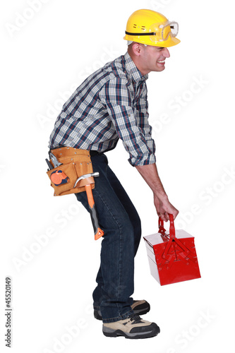 A construction worker with a heavy toolbox.