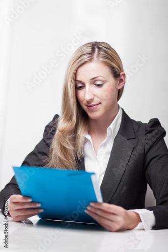 Hübsche Frau ließt ein Dokument