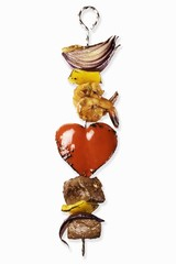 A kebab with meat, prawns, onions and a heart-shaped piece of pepper