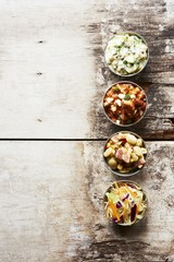Barbecue Side Dishes in Small Bowls on a Wooden Table; Pork and Beans, Potato Salad, Cole Slaw and Succotash