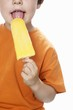 Boy eating orange ice lolly
