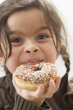 Girl holding a doughnut with sprinkles, partly eaten