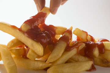 Hand taking chips with ketchup