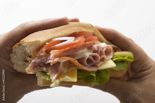 Hands holding ham and cheese sub sandwich