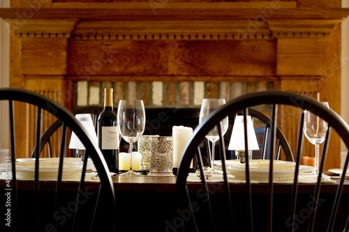 Laid table with red wine in front of fireplace