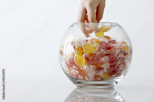Child's hand reaching into a sweet jar