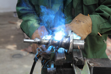 Welder doing arc welding of a steel shaft with helicoid