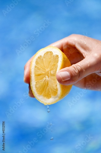 A hand squeezing a lemon