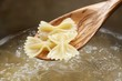 Cooked farfalle on wooden spoon above a pot