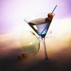Vodka Martini with Olives; Tipped Martini Glass in Background