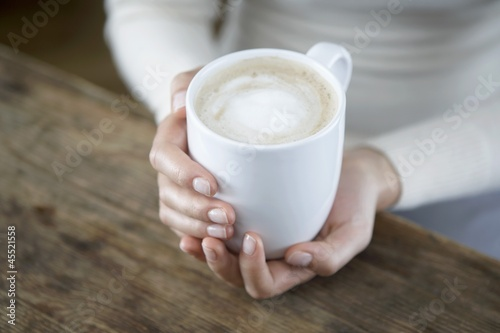 A pair of hands holding a cappuccio cup