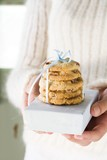 Hands holding cranberry cookies on small box