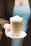 Woman holding a glass of latte macchiato