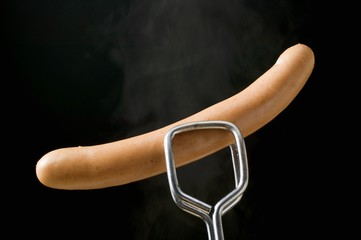 Tongs holding frankfurter