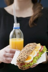 Woman holding sandwich and bottle of orange juice